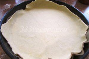 <p>Тесто делим на 2 части и раскатываем в тонкие пласты. Первый пласт выкладываем в смазанную растительным маслом форму, дно которой застелено пекарской бумагой.</p>