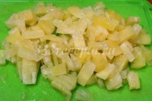 <p>Консервированные ананасы режем на небольшие кусочки.</p>