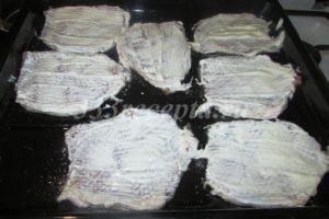 <p>На каждый кусок мяса выкладываем по 1 чайной ложке сметаны и распределяем её по всему кусочку.</p>