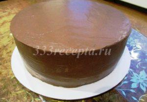 <p>Покрываем весь торт оставшимся кремом: с помощью кондитерского мешка наносим вертикальные полоски крема по всей боковине торта, затем разравниваем шпателем, потом покрываем кремом верх торта и также разравниваем шпателем. Покрытый торт убираем на 2-3 часа в холодильник.</p>