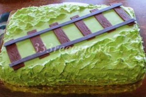 <p>Затем снова покрываем ганашем торт и с помощью силиконовой лопатки делаем травку, а по диагонали выкладываем рельсы и шпалы из желатиновой мастики.</p>
