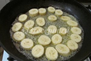 <p>Займёмся бананами: 200 г очищенных бананов нарезаем ломтиками толщиной 0,7-0,8 см. На сковороде подтапливаем 33 г сливочного масла и всыпаем 38 г сахара. Когда сахар начал плавиться, выкладываем бананы в один слой.</p>